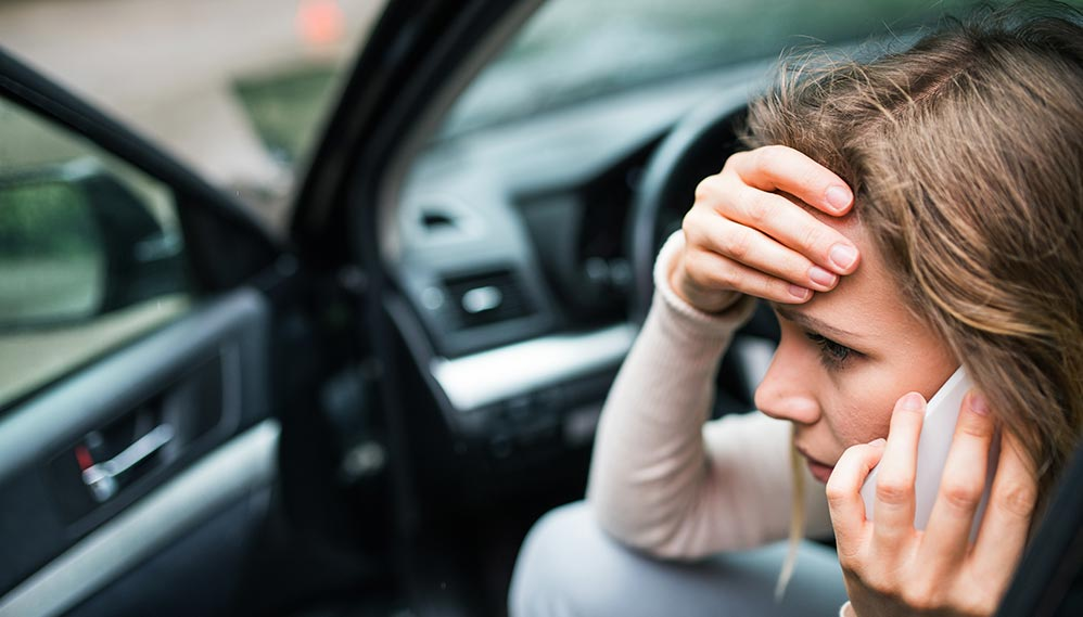 Woman calling an auto accident injury attorney from her mobile phone following a car accident.