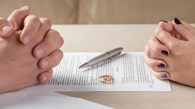 Husband and Wife signing divorce papers with wedding bands on table.