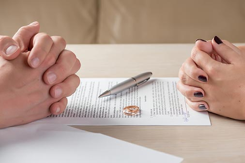 Family attorney helping couple sign legal documents
