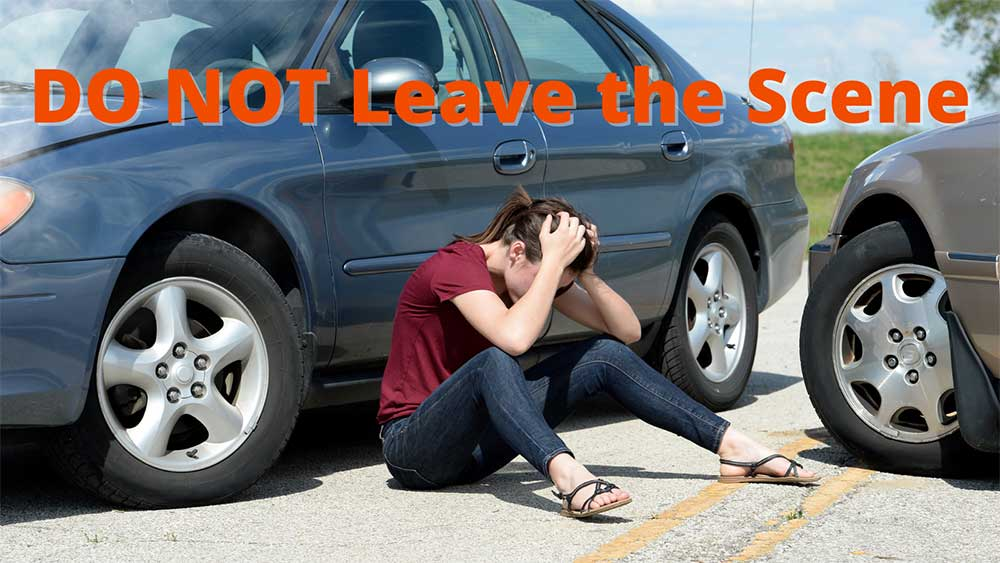 Woman visibly upset after a car accident injury with text that says Do not leave the scene.