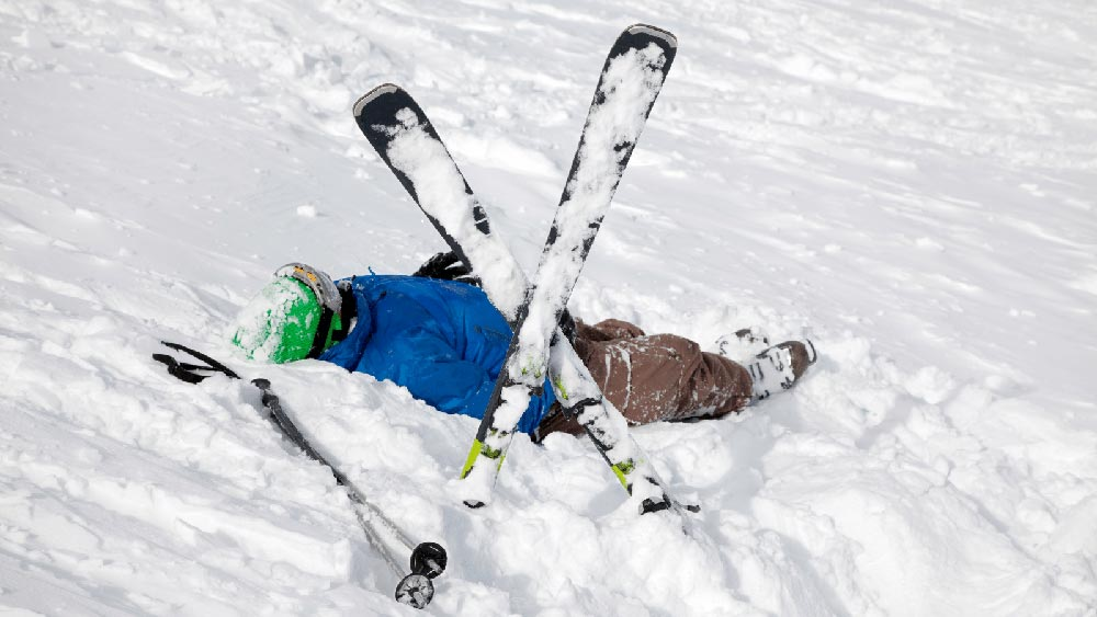 A person lying in the snow after a ski accident with their skis crossed so that other skiers know they are injured.