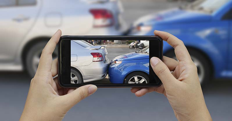 Reporting an auto accident and taking photos with a mobile phone to help document the crash scene.